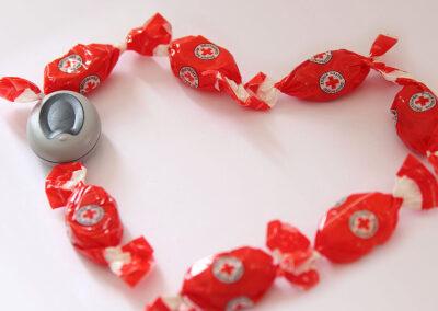 Notrufknopf und rote Bonbons als Herz aneinandergereiht