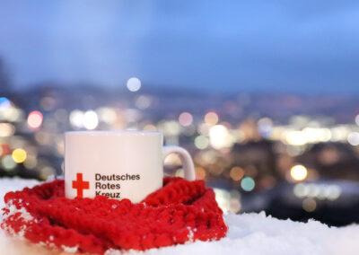 DRK-Tasse mit heißem Tee, eingehüllt in Strickschal vor Stuttgarter Winterlandschaft