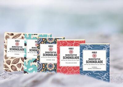 4 unterschiedlich gestaltete Schokoladenverpackungen, aufgereiht in Strandsand